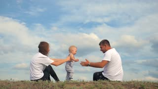 Happy family sitting together on the green grass. Family having fun outdoor. Happy young family spending time together outside in green nature on vacation outdoors. The concept of family holiday.