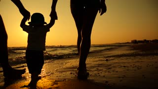 Happy family walking on sea coast. Happy family with a child on vacation at the beach. Silhouettes sunset.