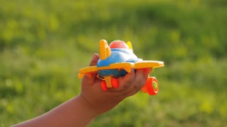 Happy kid playing with toy airplane. Children play in the backyard of the house.