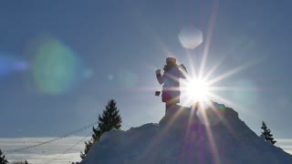 Happy little girl climbs the hill and sliding in the snow. Beautiful sunny day, the child is having fun playing with snow.