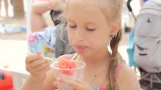 Happy little girl eating watermelon slices on the beach. Summer holiday picnic outdoors.