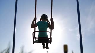 Happy little girl have fun sway spin on a swing on nature sunset. A silhouette young girl swings on a swing.