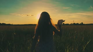Happy little girl playing with a paper airplane outdoors during sunset. Silhouette at sunset. Concept big dream.