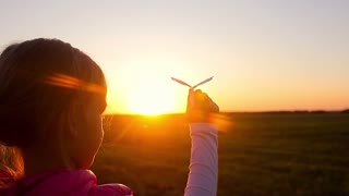 Happy little girl playing with a paper airplane outdoors during sunset. Silhouette girl holding per rocket at sunset. Concept big dream.