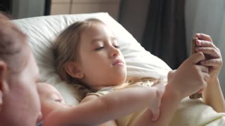 Happy mother and her young children taking selfie with smartphone on bed