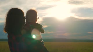Happy mother playing with little son at sunset. Young caucasian mom and baby boy having fun outdoor in evening.