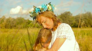 Happy mother with cute little daughter lying down on fresh green grass field, joyful family with pleasure spending time together outdoors, enjoying summer holidays