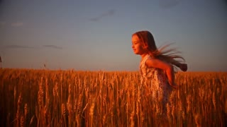 Happy running girl on a wheat field in the sunlight.