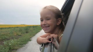 Happy teenage girl leaning out of car window. Vacation concept.