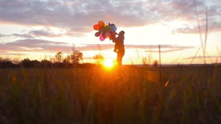 Happy young dad with daughter walking in the golden field at sunset,holding a balloons in the hand.