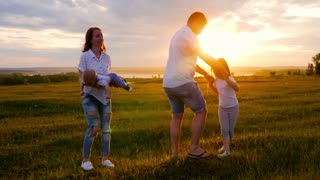 Happy Young Family with two children running on summer field. Healthy mother, father and little children enjoying nature together, outdoors at sunset.