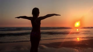 Happy young girl enjoying freedom with open hands on sea. Cheering girl hiker open arms at sunset seaside beach.