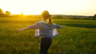 Happy young girl running on feather grass field in sunset light. Nature lifestyle and amazing view around.