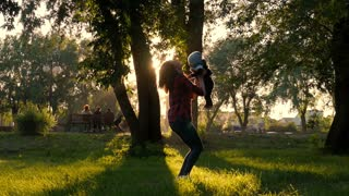 Happy young mother playing and having fun with her little baby son on sunshine warm spring or summer day. Beautiful sunset light in park. Happy family concept. Mom and son walking in a park.