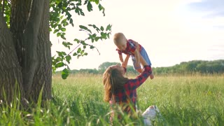 Happy young mother playing with her little baby son on sunshine warm autumn or summer day. Rainbow in the sky. Happy family concept.