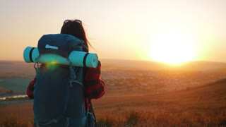 Hiker woman with a backpack on top mountains at sunset. Travel concept.
