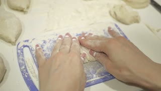 Home food. Making dough by female hands on kitchen table. Hands kneading dough on white table