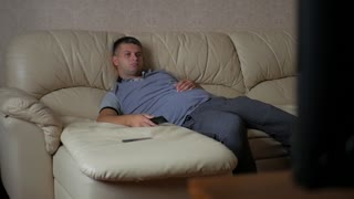 Home, people, technology and entertainment concept, man with remote control watching tv at home.