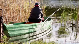 Inveterate fisherman in a boat on the lake. Summer day fishing. Wooden boat on the lake. Moored boats for fishing on the lake at the shore.