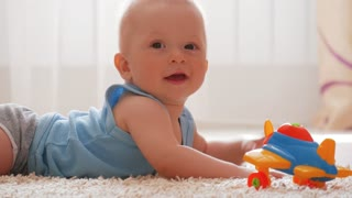 Kid boy playing with toy at home. Cute baby boy in pajamas crawling on floor and playing with toy.