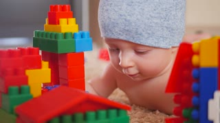 Kid playing with colored blocks of a constructor on floor in children room.