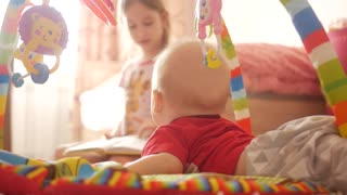 Kids playing together at home. Adorable laughing girl and a funny little baby boy, brother and sister, playing on the floor. Toys for young children.