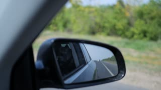 Landscape in the side view mirror of a car, on road countryside.