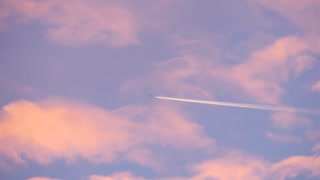 Large passenger jet flying high in colorful sky, leaving long white trail