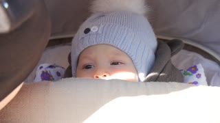 Little and very beautiful boy sitting in the pram