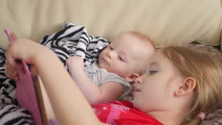 Little baby boy and girl playing with tablet computer on the bed
