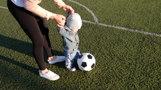 Little baby boy and his mother playing with the soccer ball at football field.