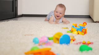 Little baby boy of seven months, crawling on the floor at children room. Kid crawling on the carpet, back view.
