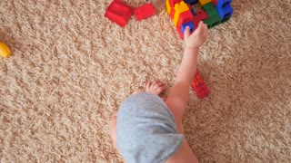 Little baby boy playing with colourful small blocks of a constructor in the room on the floor. Boy busy with his building kit.