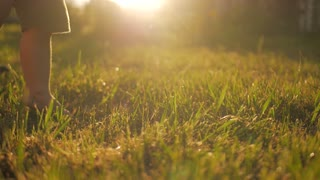 Little baby learns to walk. Slow Motion. Child to do the first steps on a green grass in summer at sunset. Close up on feet.