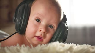 Little baby listening to music with big headphones