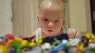 Little Baby Plays On The Floor. Close-up portrait view. Small smiling baby with a toy.
