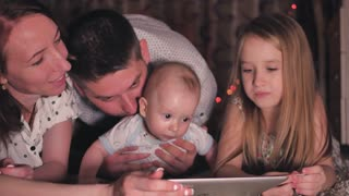 Little boy and his family are sitting together with tablet PC at night.