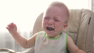 Little boy is crying because he doesn't want to eat more cereal. The concept of parents, lifestyle, feeding children.