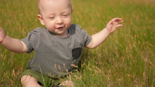 Little boy sitting on meadow and tear off green grass. Happy baby boy playing with grass on green field at summer day.
