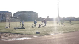 Little Boys playing soccer on the sports field next to goal. boy is playing football in the sunshine day.