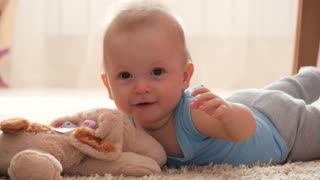 Little child baby boy lying on the floor carpet indoors in baby room
