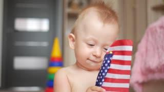 Little child boy holding an american flag.