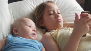 Little cute sister and baby brother is looking or playing with a smartphone on bed at home