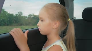 Little girl, bored in the car looking out the window.