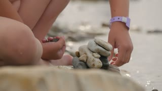 Little girl builds a pebble tower sitting on the beach by the sea. The concept of a child's dream.