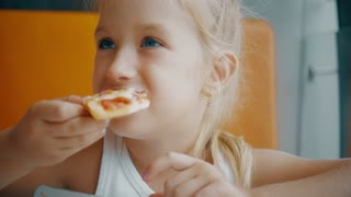 Little girl eating pizza in a fast food restaurant indoors, last piece. Funny little girl eating pizza and smiling at camera.
