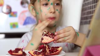 Little girl eats juicy pomegranate indoors, looking at the tablet computer. The girl is sick with chickenpox, her face is in green spots. Closeup.