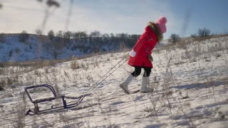 Little girl enjoy a sleigh ride. Child sledding. Toddler kid riding a sledge. Child play outdoors in snow. Outdoor fun for family Christmas vacation.