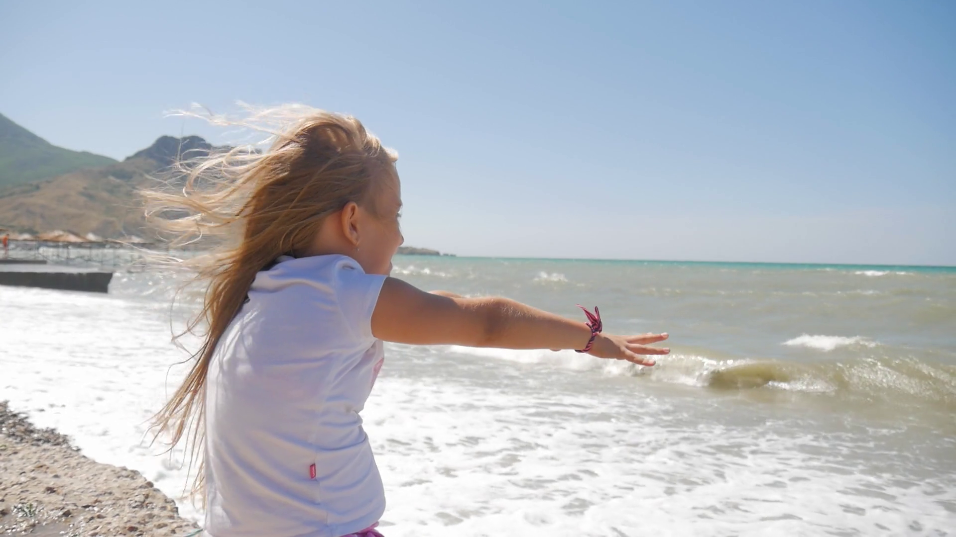 Little girl happily playing with waves at the beach. Stock Video Footage - Storyblocks