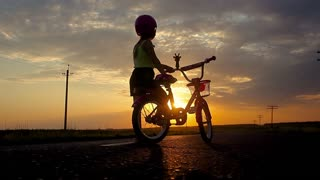 Little girl having fun riding bike at sunset, active family sport, active kids sport, Silhouette a kid at the sunset, Moments of family happiness. Orange-blue sky background.